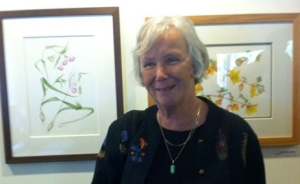 Joan Keesey with two of her paintings at the Theodore Payne Foundation.