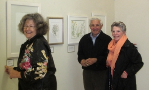 (right to left) Polly Jones, Polly's husband and Estelle DeRidder place artwork labels.