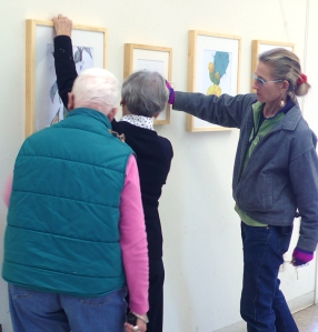 (left to right) Leslie Walker, Joan Keesey and Lesley Randall hang and straighten artwork.