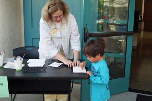 BAGSC member Melanie Campbell-Carter assists an exhibition visitor with a leaf rubbing. Photo by Lori Vreeke, © 2015.