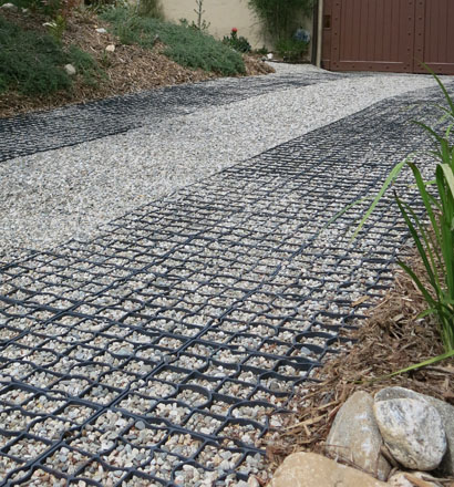 Permeable gravel surfaces finished with StabiliGrid tiles hold gravel in place and provide ADA-compliant wheelchair accessibility for the driveway and garden. Photo © 2016, Cordelia Donnelly.
