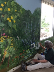Estelle DeRidder adding details to the mural. Photo by Leslie Walker, © 2017.