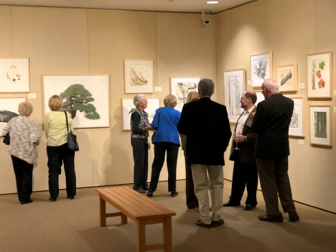 "Guests enjoying the ""Out of the Woods"" exhibition."