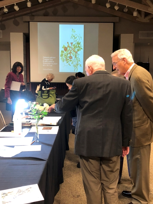 Guests viewing the botanical art demonstrations, with images from the ASBA Worldwide exhibition in the background.
